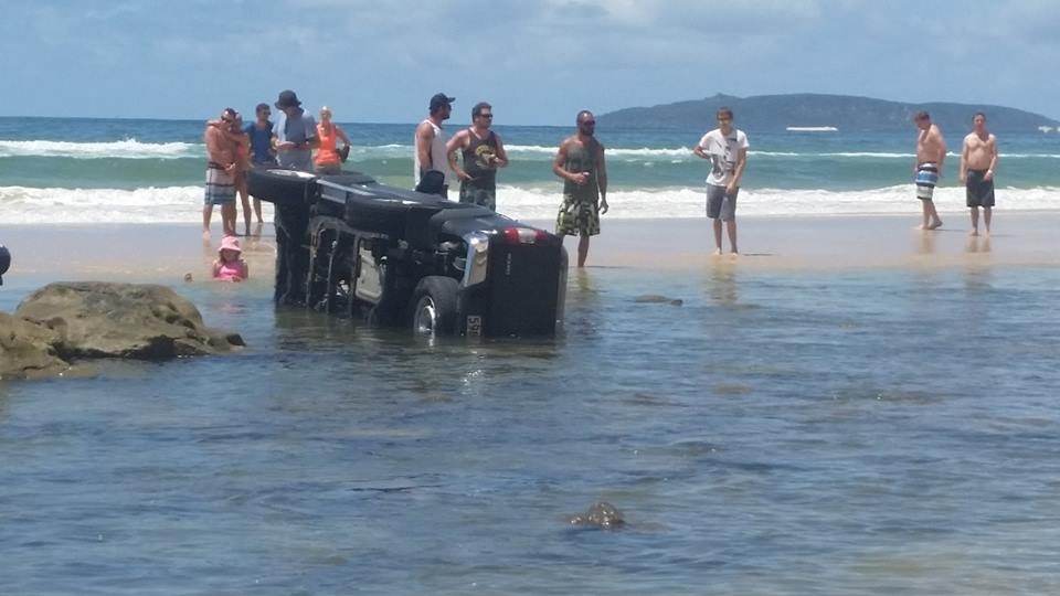 An upturned vehicle on the beach makes for considerable deliberation.